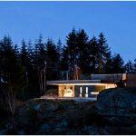 Очаровательный и уютный дом с панорамными окнами на фоне суровых скал